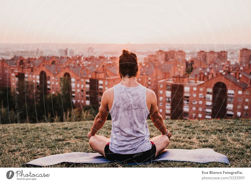 young man in a park ready to practice yoga sport. city background. healthy lifestyle. Concentrate Position Human being Youth (Young adults) Body Park Man