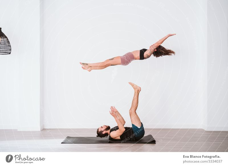 young couple Couple practicing acro yoga in white studio or gym. Healthy lifestyle Yoga Sports Gymnasium Man Power Human being