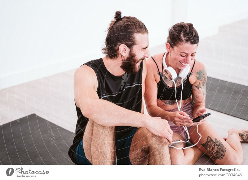 two friends at the gym listening to music on mobile phone and headset and having fun. Sport and technology concept Couple Friendship Youth (Young adults) Man