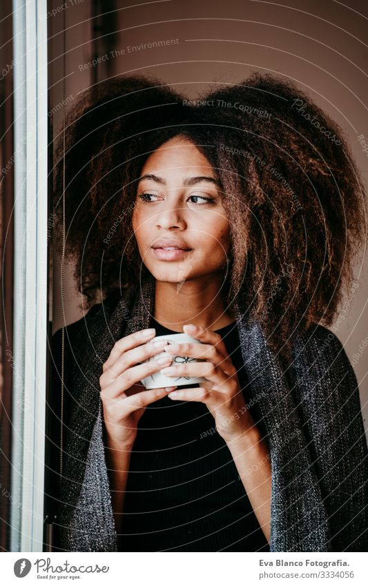 portrait of beautiful afro american young woman by the window holding a cup of coffee. Lifestyle indoors African-American Woman Coffee Home Ethnic