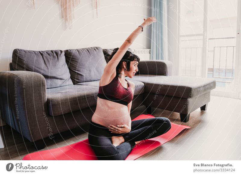 young pregnant woman at home practicing yoga sport. healthy lifestyle Pregnant Woman Yoga Home Sports Healthy Lifestyle Youth (Young adults)