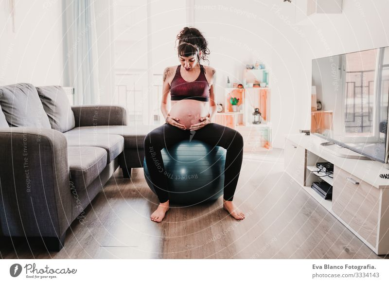 young pregnant woman at home sitting on pilates ball, healthy lifestyle Pregnant Woman Yoga Home Sports Healthy Lifestyle Youth (Young adults)