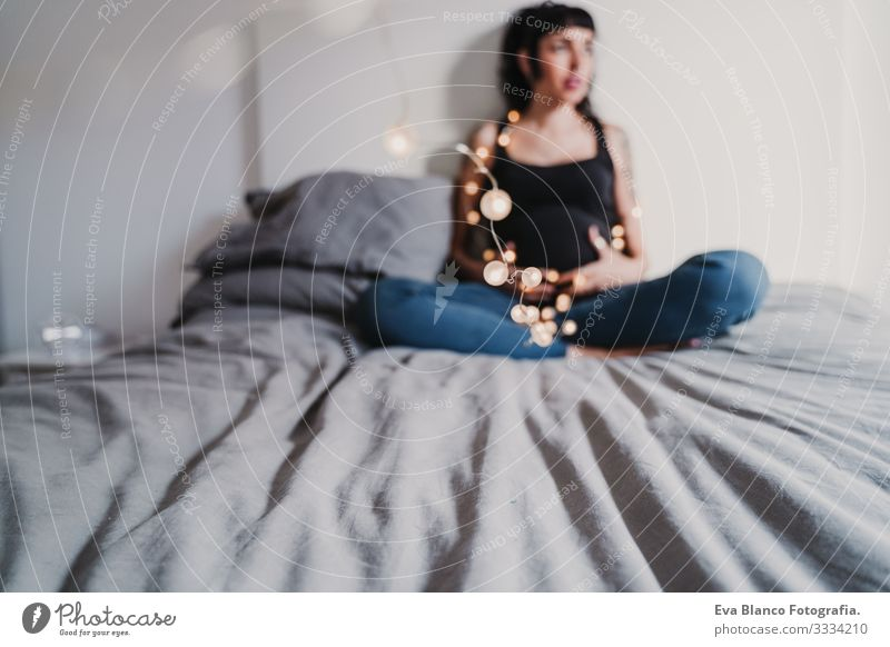young pregnant woman at home holding a garland of lights Pregnant Woman Home Paper chain Light Christmas & Advent Smiling Happy Portrait photograph