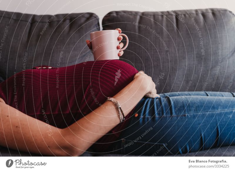 portrait of young pregnant woman at home lying on the sofa and holding a cup on belly Pregnant Woman Portrait photograph Home Lifestyle Window Day