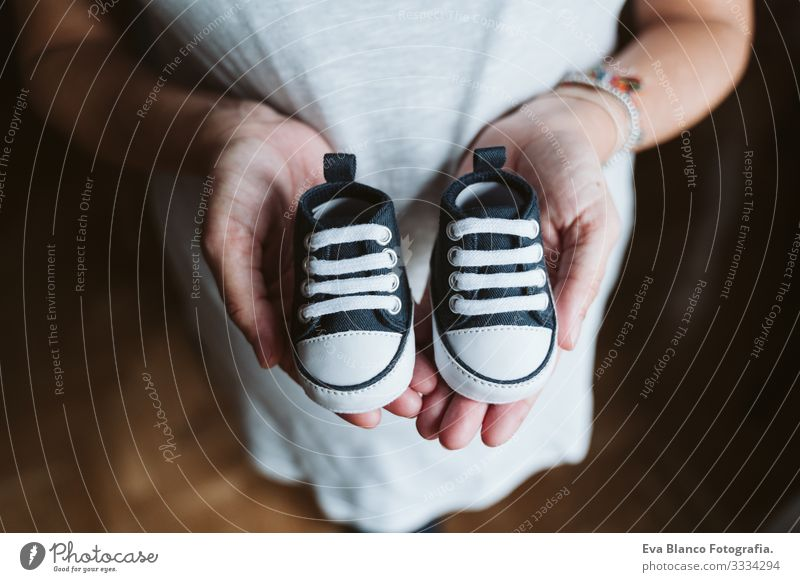 young pregnant woman at home holding baby shoes Pregnant Woman Home Bed pregnancy Baby expecting Showing one's bellybutton Day Lie tenderness pleasure