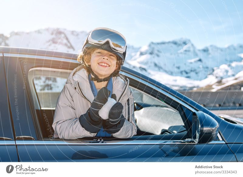 Cheerful boy making snowball in car winter smile roll resort sunny daytime kid child recreation lifestyle happy cheerful delighted optimistic vehicle auto