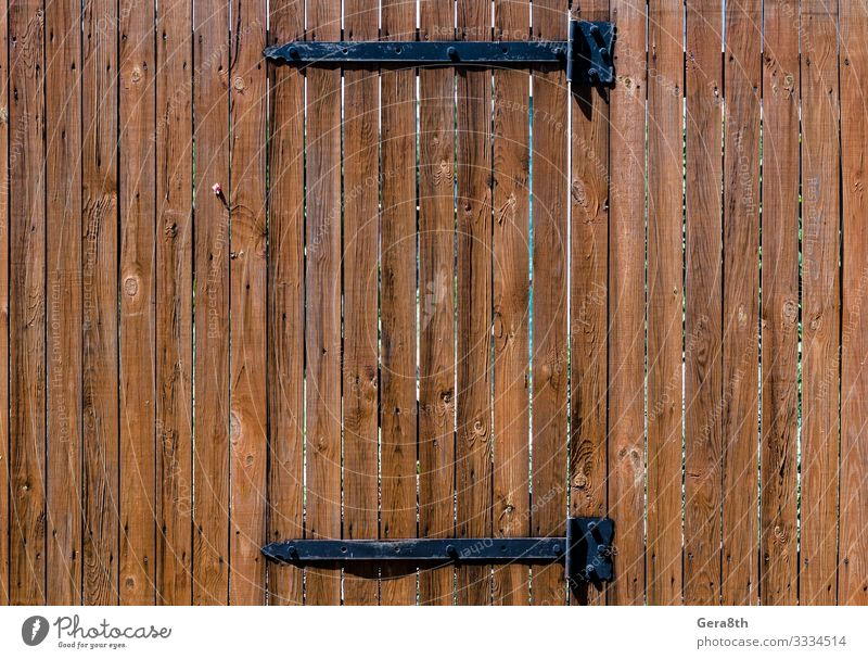 texture wooden fence with a wooden door on iron hinges Wood Brown billet Fence natural tree Consistency Wooden door Colour photo Exterior shot Pattern Day