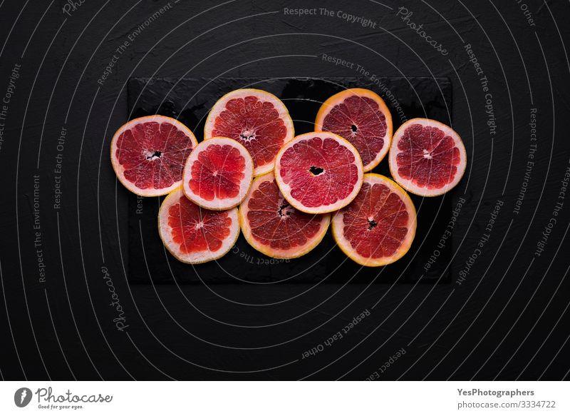 Grapefruit slices on a black table. Sliced fresh citrus fruit Food Fruit Breakfast Healthy Eating Fresh above view antioxidant fruit black background