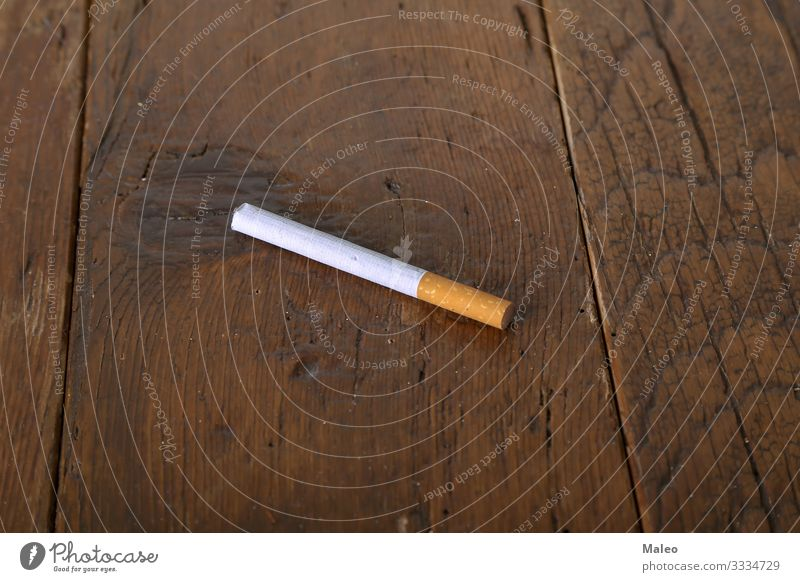 Filter cigarette lies on a wooden table Addiction Cigarette Concepts &  Topics Health care Lifestyle Smoke Tobacco Close-up Consumption Costs Industry Leaf