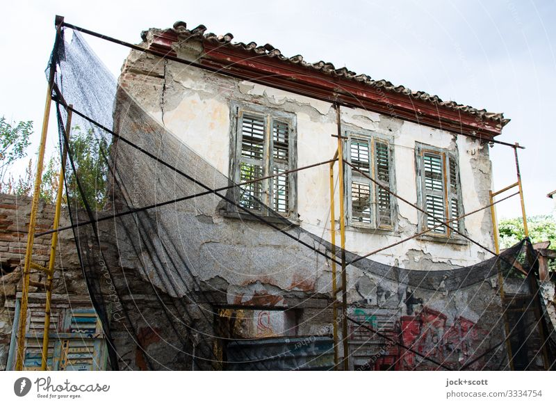 gloss and misery lost places Sky Summer Climate change Greece Old town Ruin Facade Window Scaffolding Net Remainder Authentic Sharp-edged Broken Warmth Moody