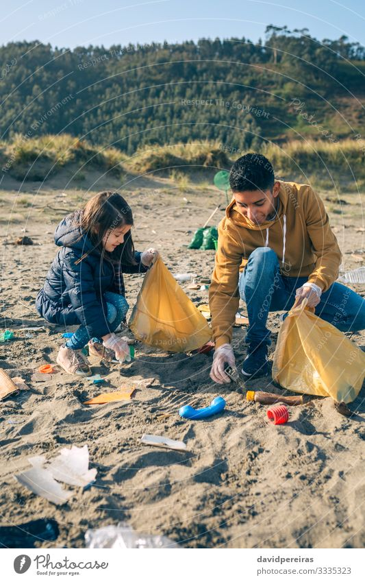 Young volunteers cleaning the beach Woman Child Human being Man Joy Beach Adults Environment Happy Work and employment Sand Dirty Smiling To enjoy Plastic Trash