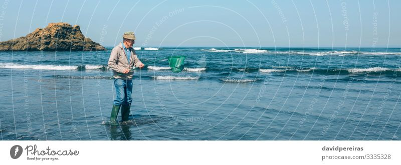 Volunteer taking garbage out of the sea Beach Ocean Work and employment Internet Human being Man Adults Grandfather Environment Nature Landscape Rock Coast Hat