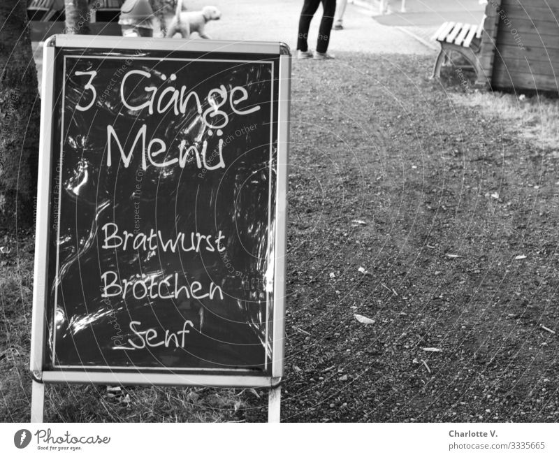 The display board of a snack bar promises a three-course menu consisting of bratwurst, bread rolls and mustard for purists. Culinary delights in black and white.
