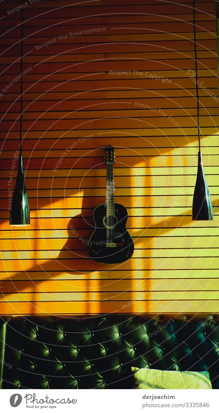 Guitar on the wooden wall. With right and left two hanging lamps and below a leather sofa with cushions. Joy Relaxation Trip Room Environment Beautiful weather
