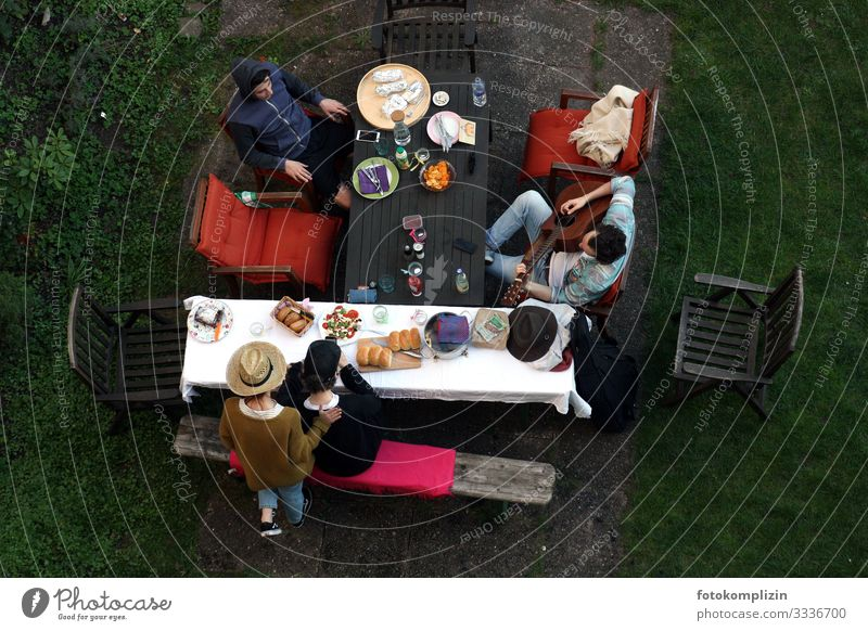 View from above of four people with picnic and guitar player at the garden table Garden table chill Together Calm fellowship Siesta Guitarist garden idyll