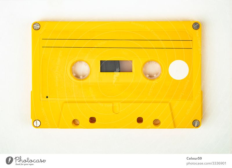 Yellow music cassette Music Retro Tape cassette audio Vintage 80s Background picture recording Analog free time tape Colour photo Studio shot