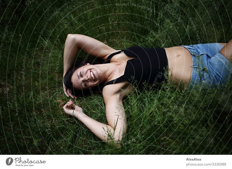 Young woman lies in the grass and laughs Joy Beautiful Life Trip Youth (Young adults) 18 - 30 years Adults Plant Summer Beautiful weather Grass Top Brunette
