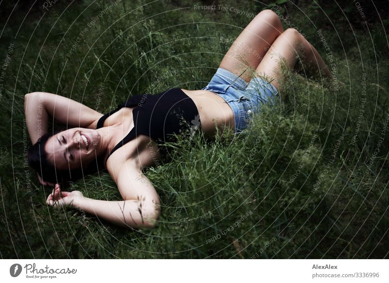 Young woman lies in a clearing in the forest Lifestyle Joy Beautiful Well-being Trip Camping Youth (Young adults) 18 - 30 years Adults Plant Summer Meadow