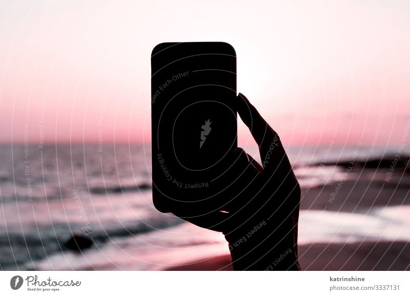 Girl is taking a sunset photo on the phone Vacation & Travel Summer Beach Ocean Cellphone PDA Technology Woman Adults Hand Environment Nature Landscape Sky Dark