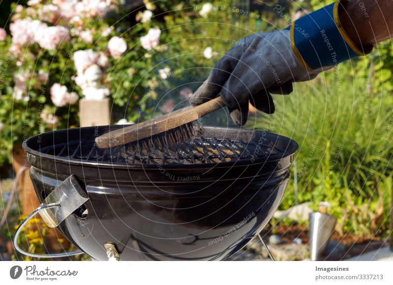 Cleaning grill. Male hand with gloves cleans round grill with brush. Preparing a grill before cooking. Man cleaning a grill in the garden BBQ Human being 1