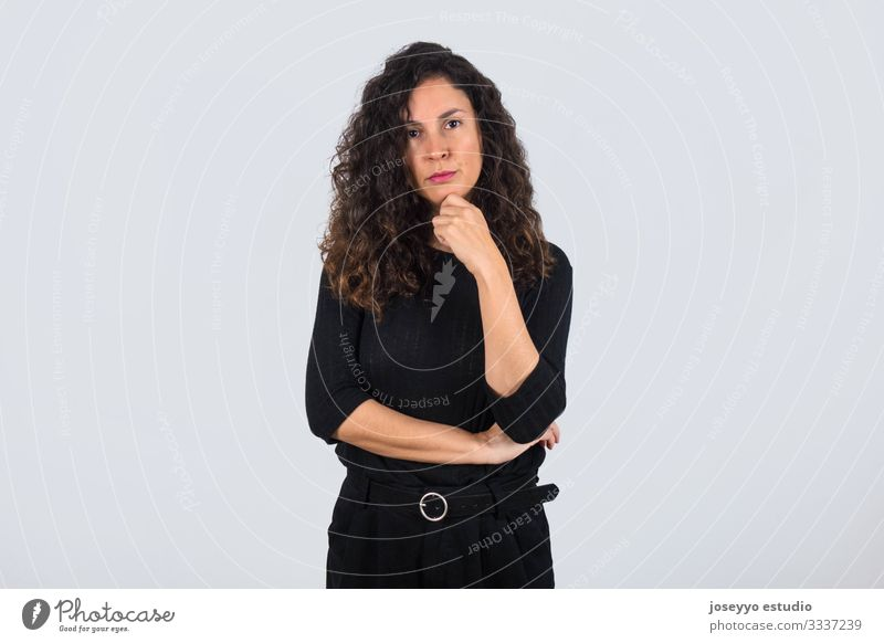 Curly-haired brunette woman dressed in black with her hand on her chin looking at camera with serious expression. 30-40 years advertisement attitude background