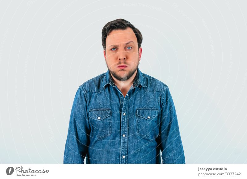 Young man with expression of tiredness and denim shirt. Isolated gray background. 30-40 years advertisement advertising apathy attitude banner beard blue eyes