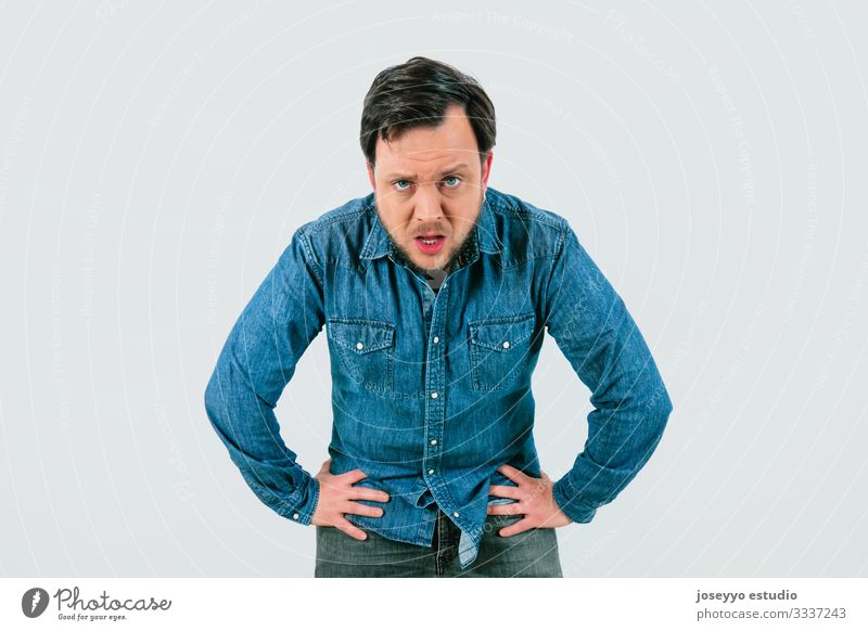 Young man with expression of tiredness and exhaustion. Denim shirt and isolated gray background. 30-40 years advertisement advertising anguish annoyance anxiety