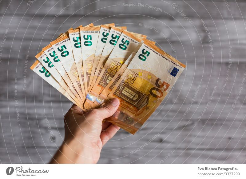 woman hand holding cash isolated on grey wood background. Euro fifty bills. European Money wealth Hold payment Financial Financial institution Business