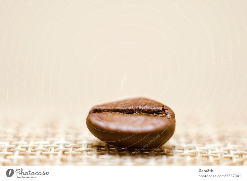 one grain of coffee on a matting macro Breakfast Coffee Cloth Dark Fresh Natural Brown Black Energy Colour Aromatic backdrop background Beans Beige blur blurry