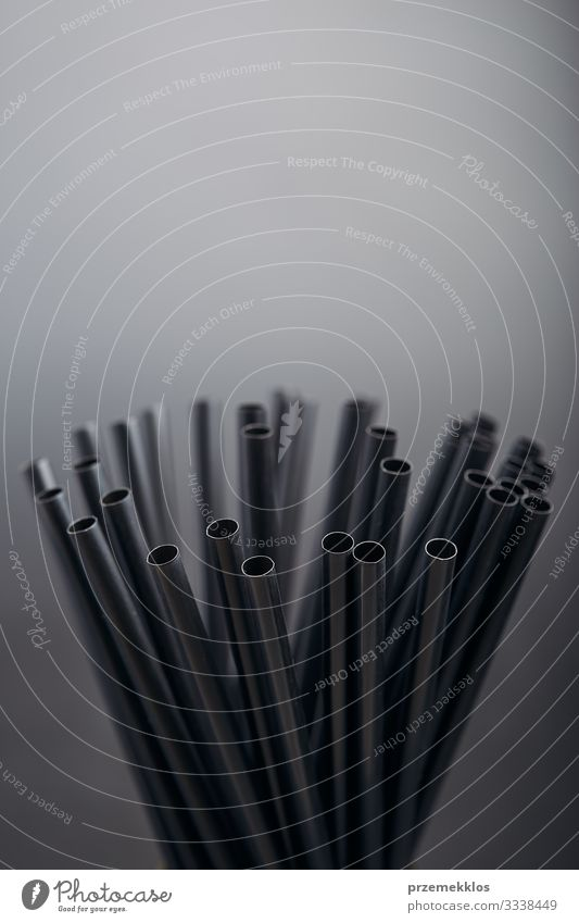 Bunch of black plastic straws scattered in container over plain grey background. Copy space for text Beverage Environment Plastic Black Environmental pollution