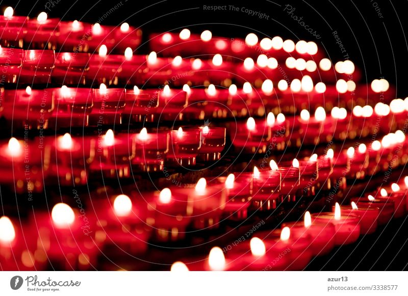 Group of red candles in church for faith resurrection prayer hope sacrifice silence grief love peace soul religion candlelight fire flames obituary obsequies
