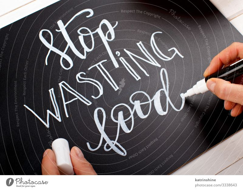 Woman writing on a chalkboard Stop wasting food lettering Body Blackboard Adults Hand Environment Pen Hip & trendy Small keeping marker Chalk ecologic