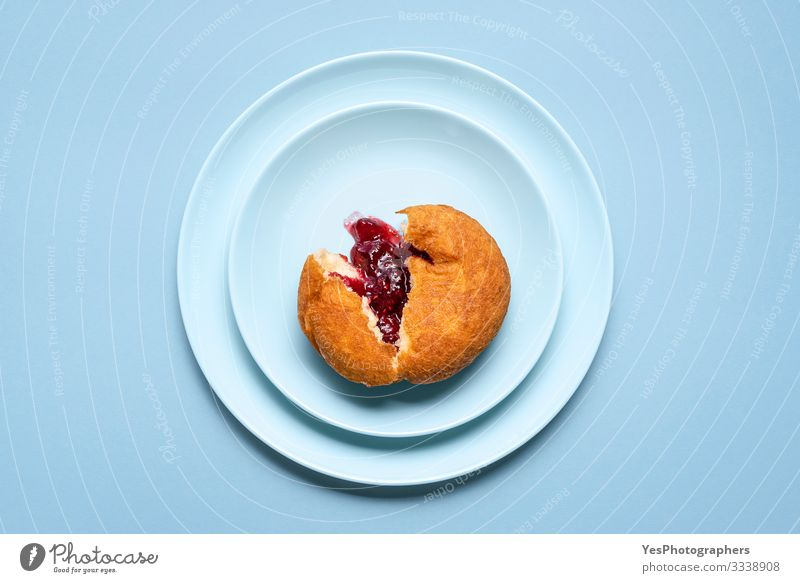 One jelly donut on a plate. German doughnut with raspberry jam Cake Dessert Candy Jam Delicious Tradition Germany above view Bakery berliner doughnuts