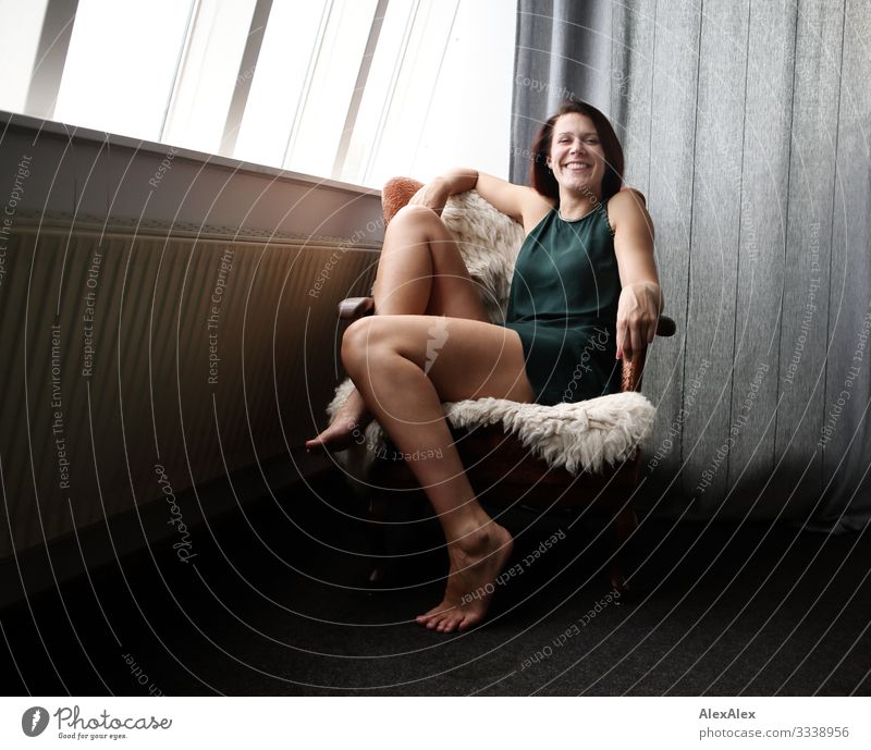 Young tall woman sitting in an armchair Style Joy Beautiful Life Living or residing Flat (apartment) Armchair Young woman Youth (Young adults) Legs