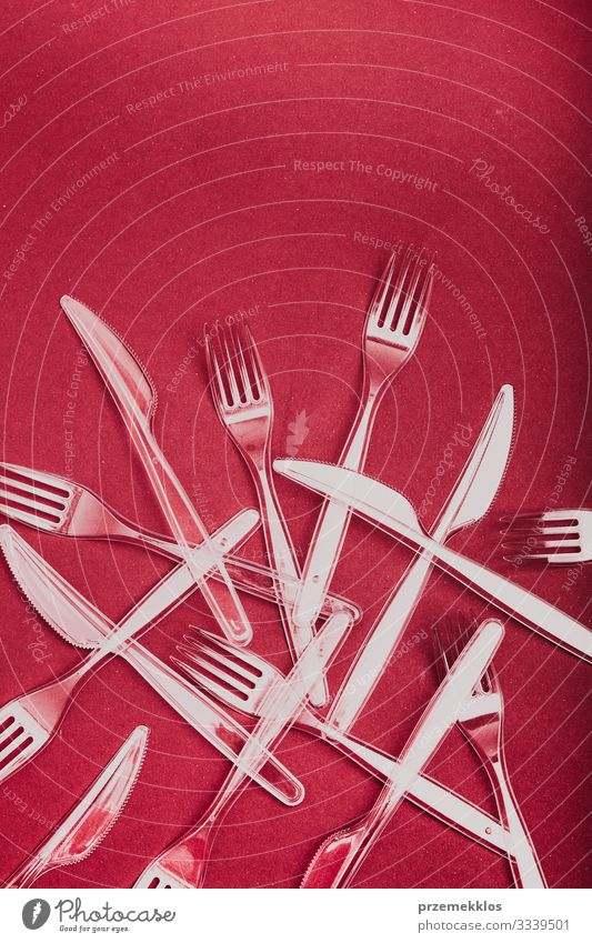 Plastic cutlery scattered over red background Cutlery Fork Save Environment Container Red Environmental pollution Environmental protection Trash garbage recycle