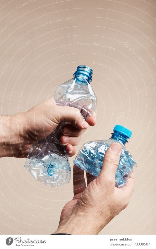 Male hand holding squashed plastic bottle Bottle Save Man Adults Hand Environment Container Plastic Blue Environmental pollution Trash garbage recycle Recycling