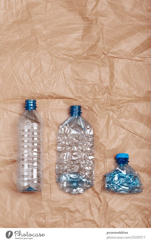 Squashed empty plastic bottles put in a row Bottle Save Environment Container Paper Plastic Blue Brown Environmental pollution Environmental protection