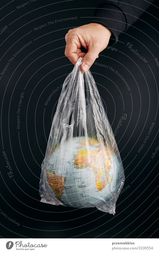 Male hand holding globe in a plastic bag. Contaminated Earth Man Green Hand Black Adults Life Environment Copy Space Plastic Sphere Trash Globe Ecological
