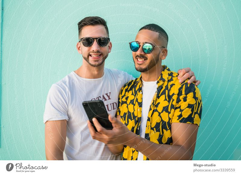 Gay couple spending time together while using phone. Lifestyle Happy Leisure and hobbies Freedom Cellphone PDA Human being Masculine Homosexual Man Adults