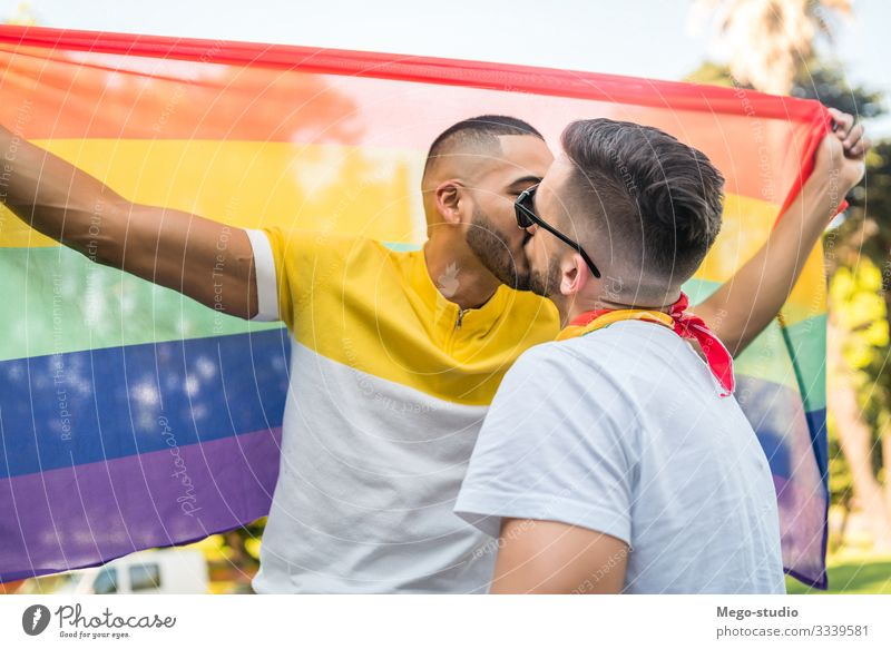Gay couple kissing and showing their love with rainbow flag. Lifestyle Happy Freedom Feasts & Celebrations Human being Homosexual Man Adults Couple Partner 2