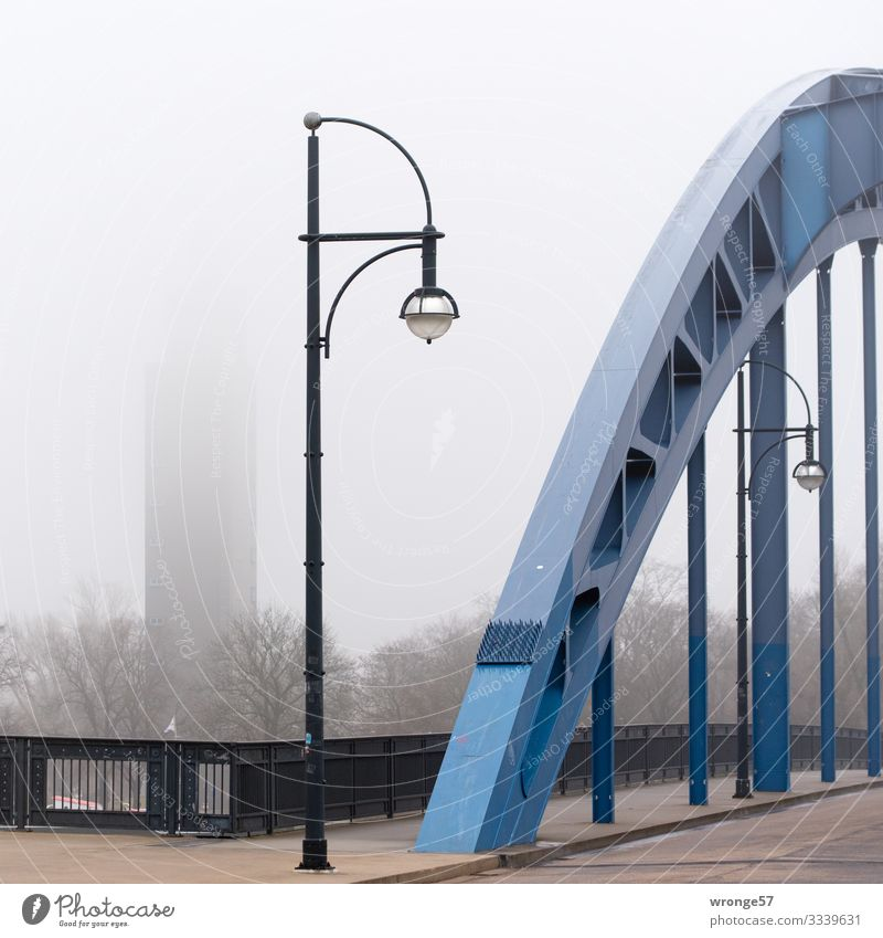 In the foreground an arch of the star bridge and in the background the Albin Müller tower on a foggy day Magdeburg Germany Europe Town Downtown Deserted Park