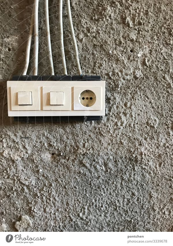 Temporary socket and light switch on a construction site. Rough plaster Technology Energy industry Energy crisis Old Poverty Hideous Cold Light switch