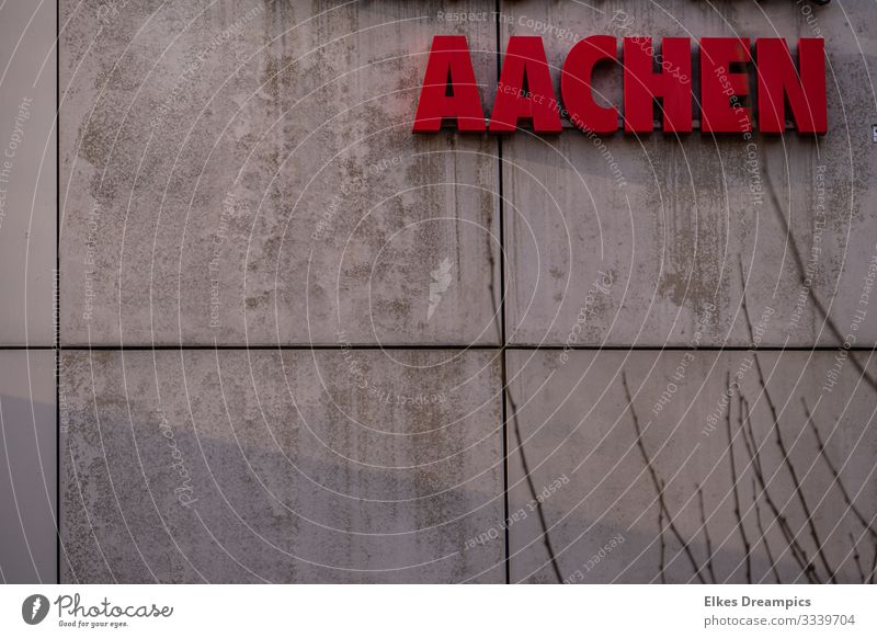 Aachen on the wall Town Downtown Building Wall (barrier) Wall (building) Facade Characters Signs and labeling Looking Esthetic Modern Red Authentic Design