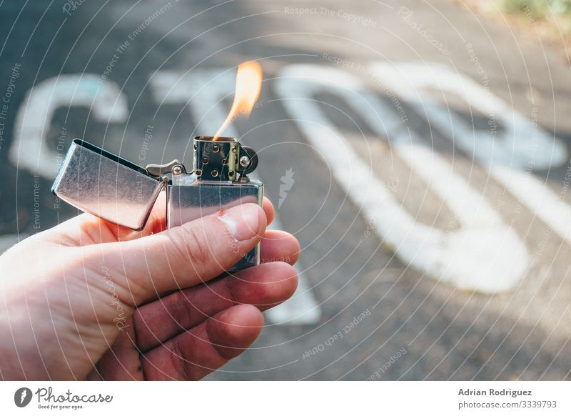 Lighter in hand lit with stop message in the background Man Adults Hand Power Protection Safety (feeling of) Dangerous Force Disaster Communication fire burn