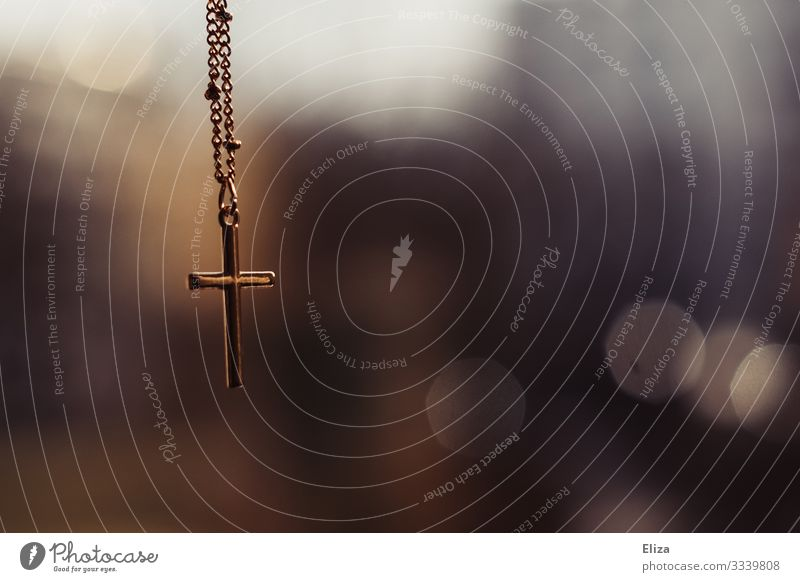A golden cross crucifix hangs on a chain in front of a blurred background in the church Crucifix Church Belief Chain Gold Christian cross Religion and faith