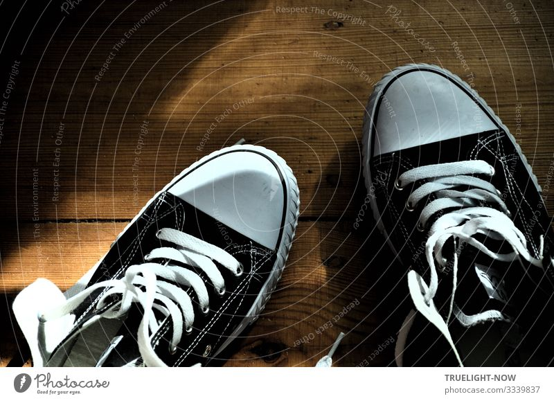 Black and white sneakers on wooden floor with sunlight and shade Sneakers Chucks Shoelace black-white Wooden floor planks Sunlight Shadow New Open slack