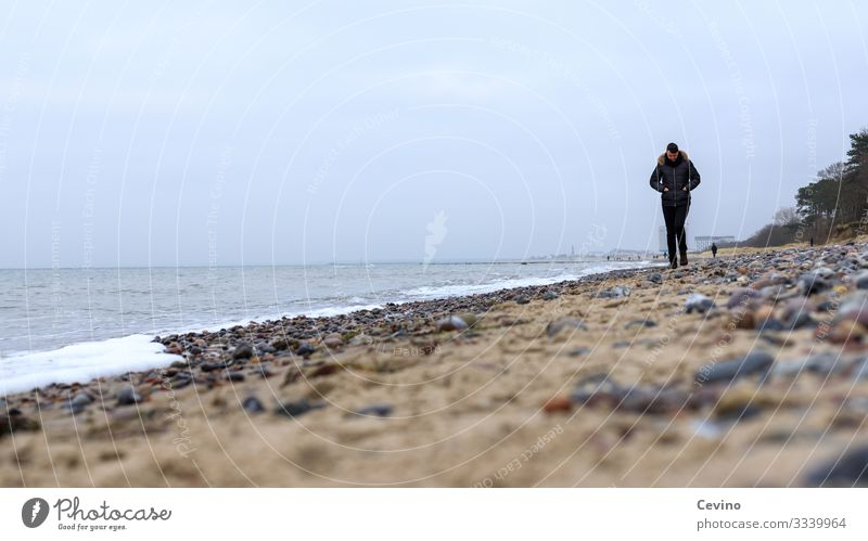 Young man strolls on the beach To go for a walk Beach Baltic Sea Lonely Loneliness thoughts vacation Waves stones Sand hike lost in thought brood young adult