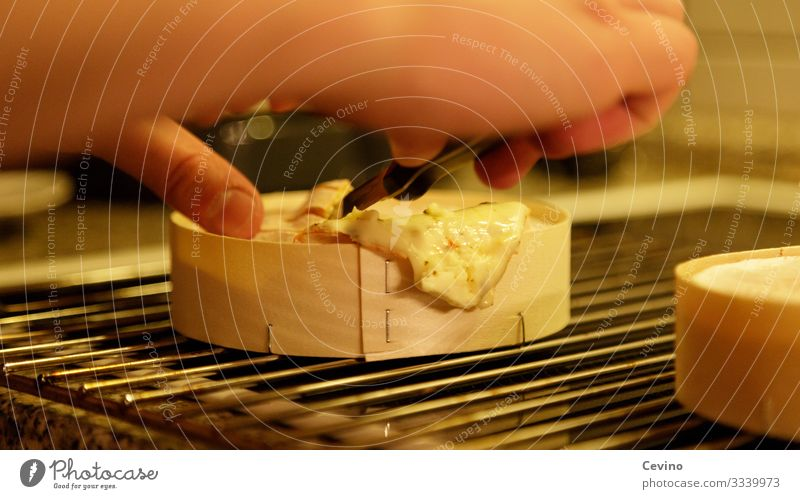 Oven cheese is divided with a knife kiln Cheese oven cheese Delicious Unhealthy Knives Rust Furnace grate Grating Hand Dinner Snack Meal Interior shot hunger