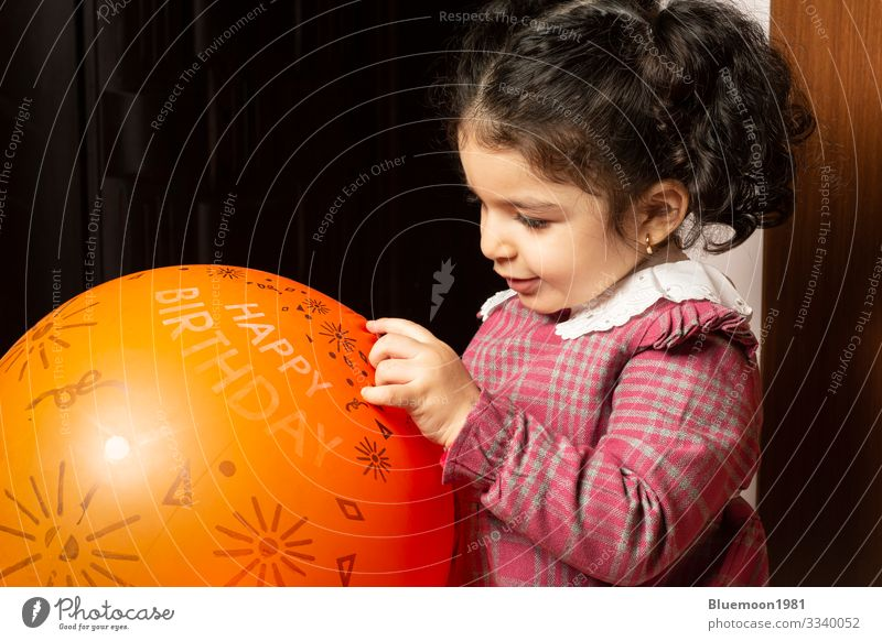 A little girl child is playing with orange birthday balloon Lifestyle Design Joy Face Playing Feasts & Celebrations Child Industry Human being Girl Infancy 1