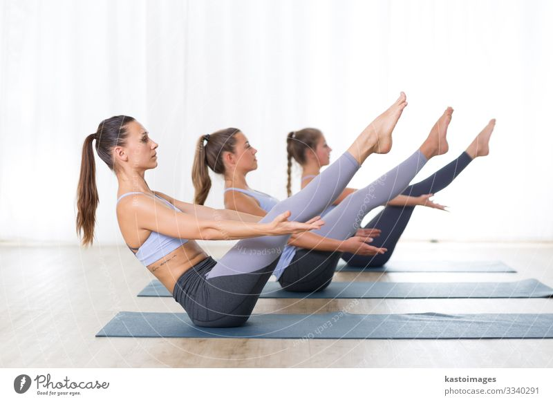 Group of young sporty attractive women practicing yoga. Lifestyle Beautiful Body Health care Wellness Relaxation Meditation Sports Yoga Human being Woman Adults